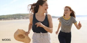 Mother and Daughter Smiling and Running Down Beach